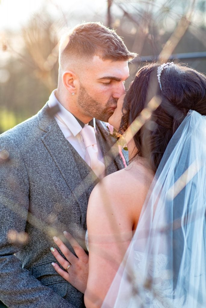 A couple share an intimate kiss at their wedding venue, The Vale Resort, Cardiff.