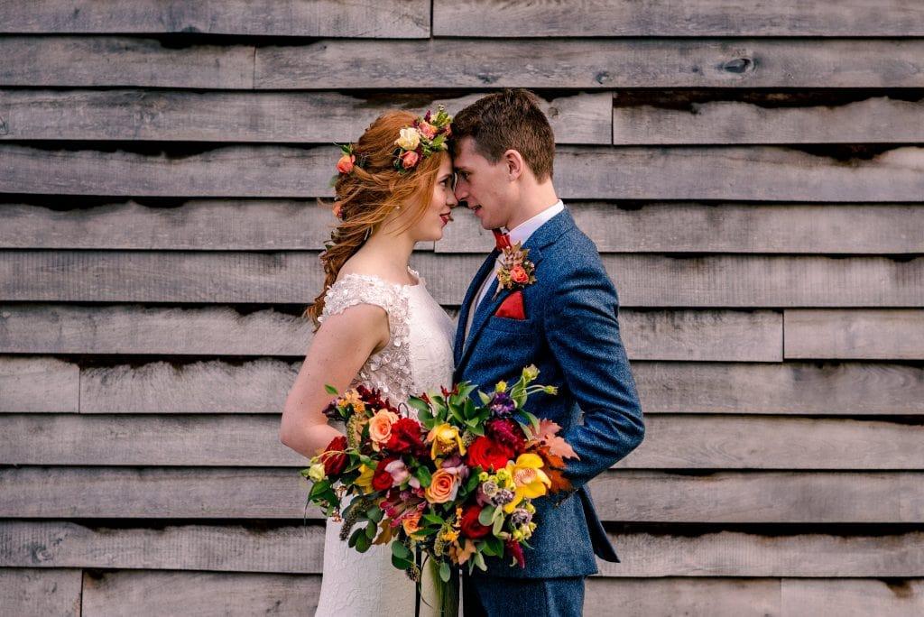 Newlywed couple embrace at The Barn At Upcote