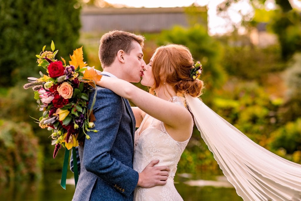 Couple kissing in the Autumnal scenes of a secret garden. Located at The Barn at Upcote and caught on camera by Pedge Photography.