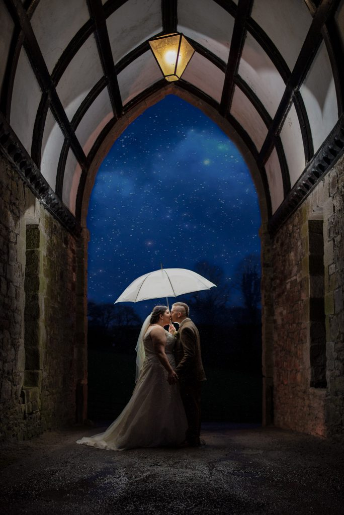 Under the arch shot at Clearwell castle. A flash lights up the archway in the dar as a couple kiss under a white umbrella.