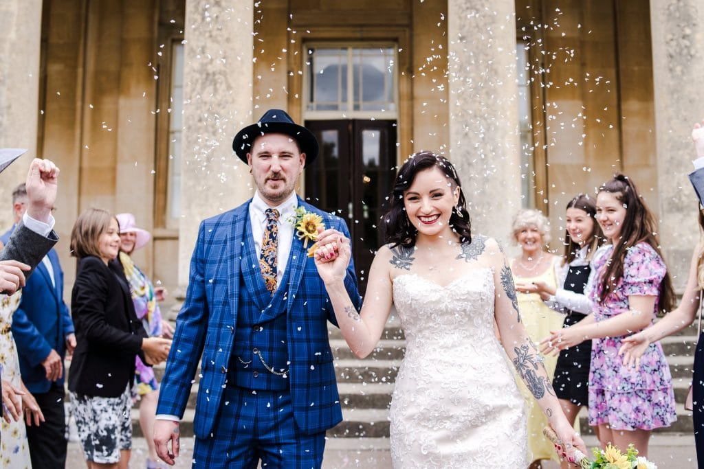 a newly married couple get covered in confettin on the steps of The Pittville Pump Rooms, Cheltenham