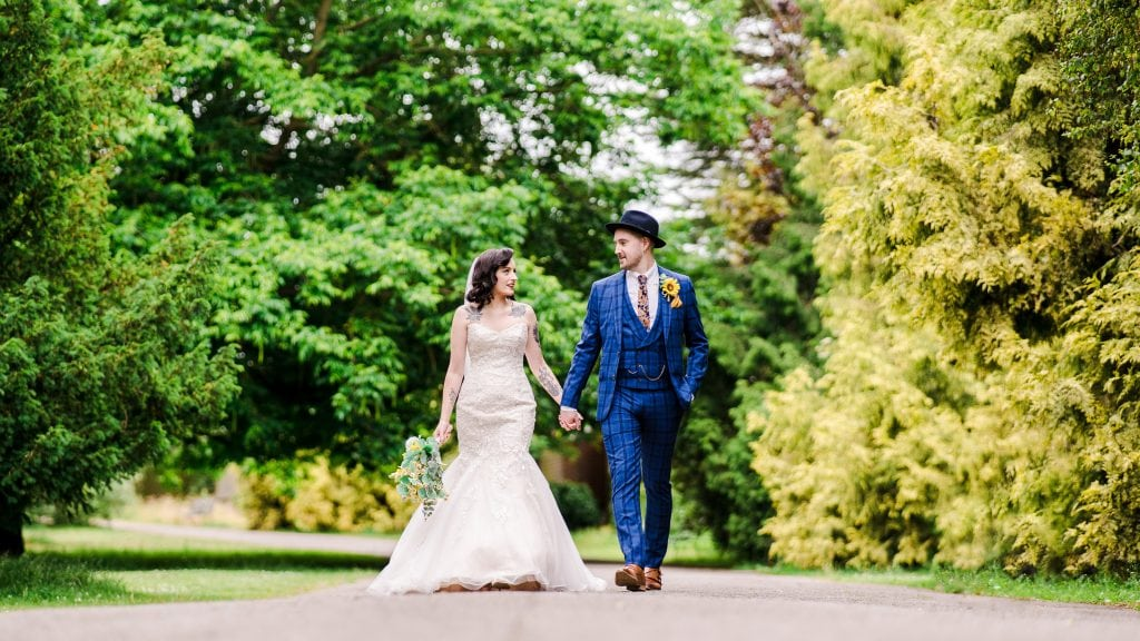 A gorgeous newlywed couple walk through Pittville Park. The bride is in a gorgeous, traditional white dress with an elegant bouquet of sunflowers. The groom is wearing a blue chequered three piece suit, matched with a bowler hat.