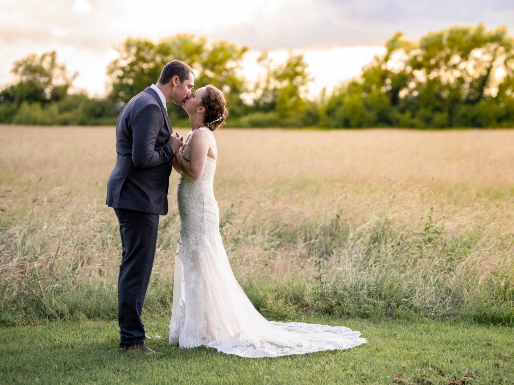 Newlywed couple at Hatherley Manor pose in the summer sun of the countryside at Hatherley Manor