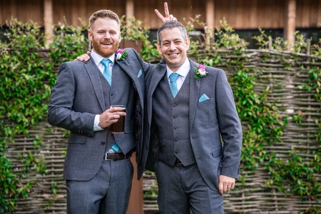 The best men of a wedding at Hatherley Manor, having their picture taken, whilst one pulls off a funny move!