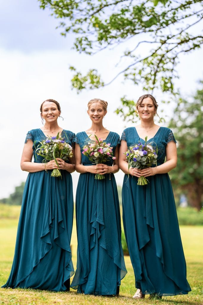 3 lovely Bridesmaids pose for a picture with their flowers on a gorgeous country backdrop, at a Gloucestershire wedding located at Hatherley Manor, Gloucester